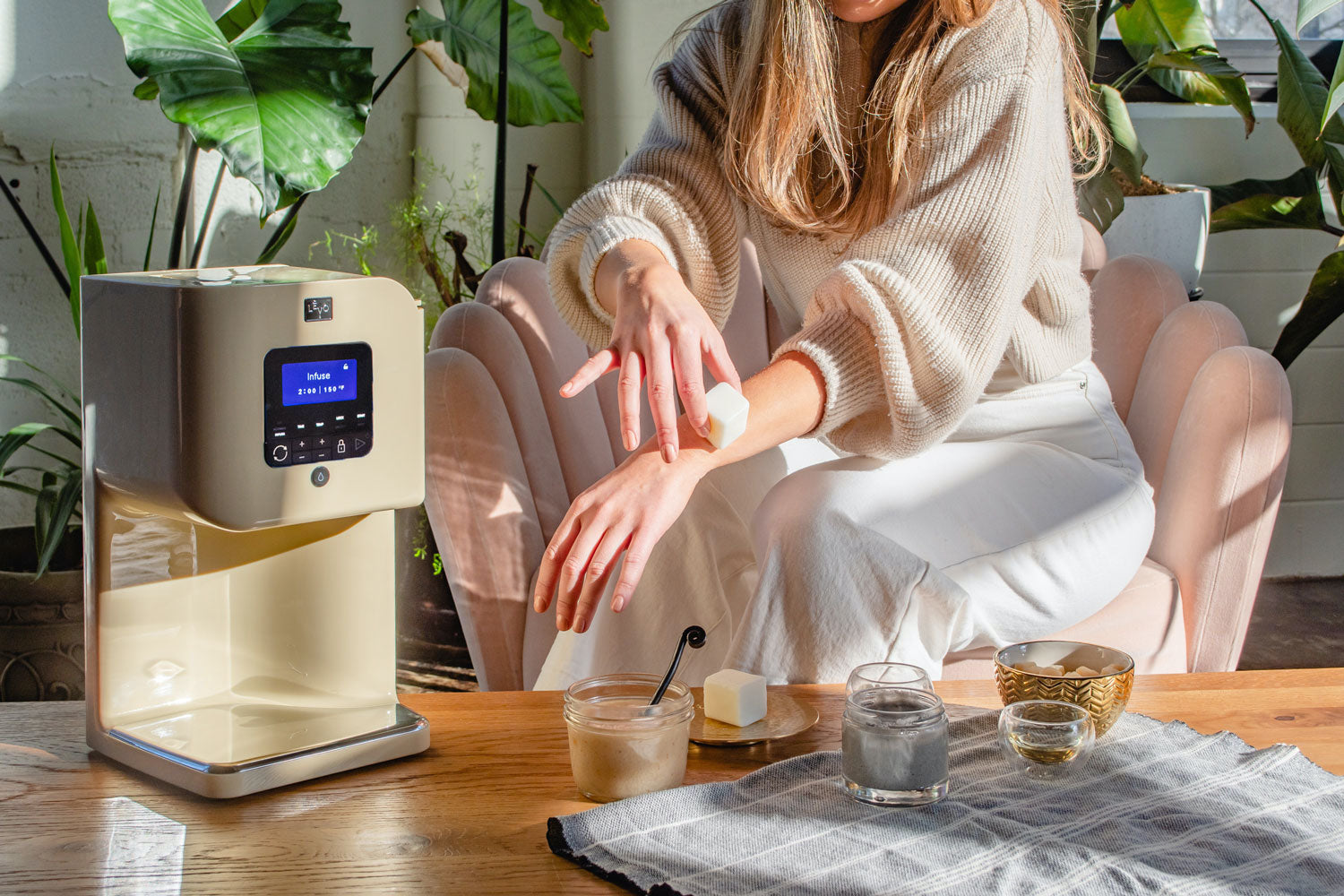 Image of a woman sitting next to a Honey Cream LEVO II machine with her DIY skincare routine.