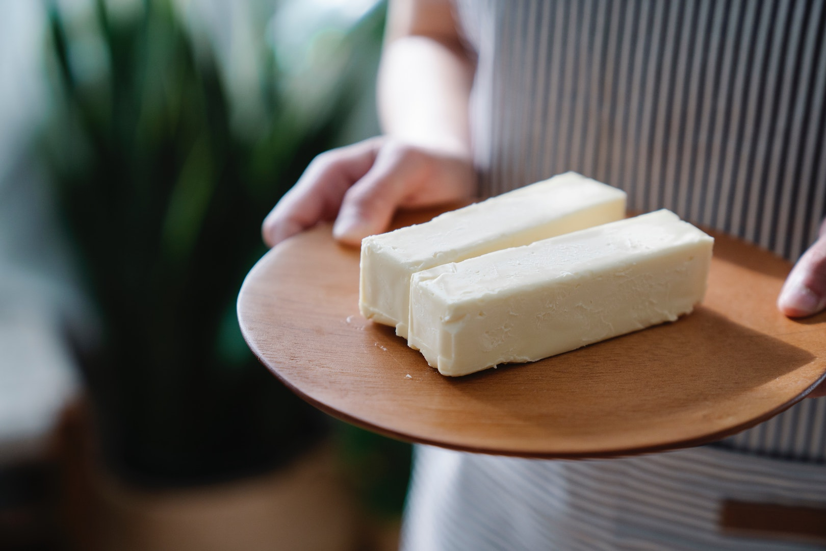 Image of person holding two blocks of cheese. Does butter go bad? Learn more with LĒVO.