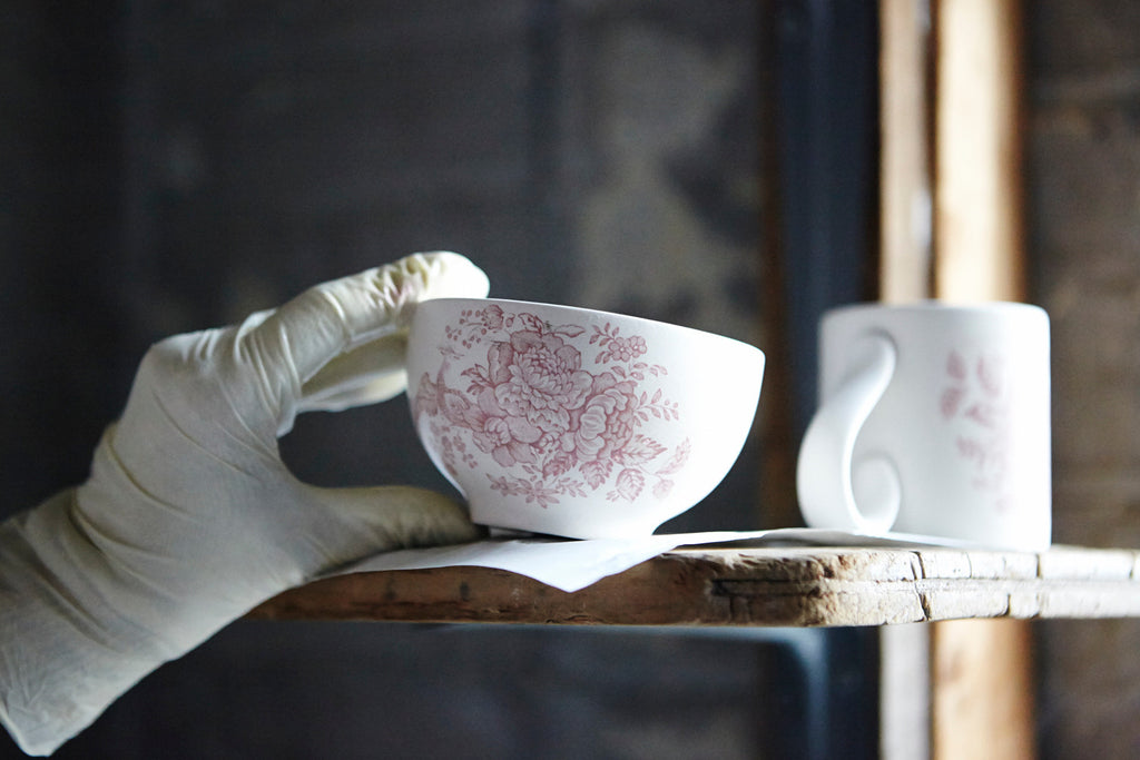 A Pink Asiatic Pheasants Rice Bowl being placed on a shelf ready for firing