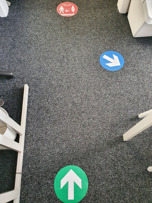 Blue and green floor stickers showing different directions