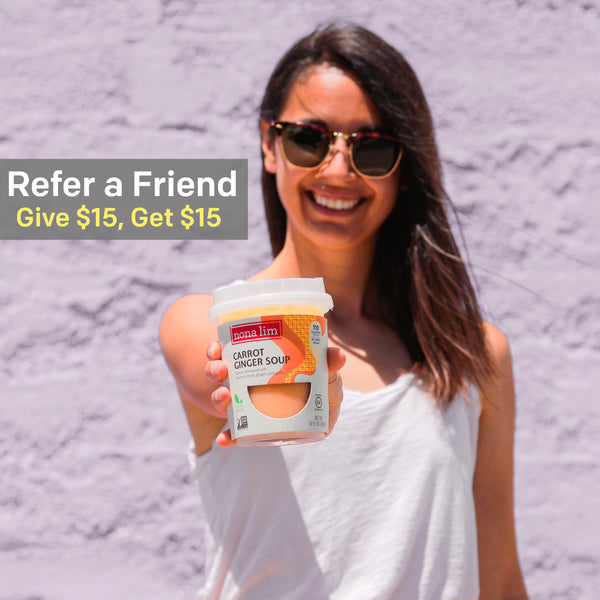 Refer A Friend, Give $15, Get 15. Woman with long hair and Dark sunglasses holding out the Nona Lim's Carrot Ginger Heat and Sip Soup Cup