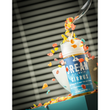 cream vapor cirrus e-liquid bottle on a table with coloured bits of cereal pouring on top of bottle