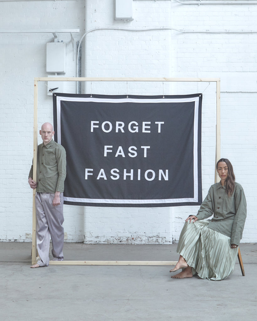 Man and woman in warehouse wearing olive-coloured Uskees overshirts and posing with 'Forget Fast Fashion' board.