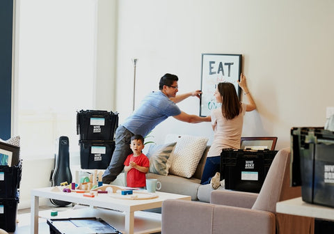 man and children hanging paintings on wall