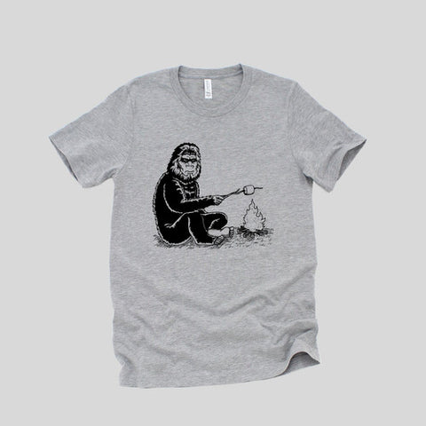 Grey tshirt with a black screenprinted design of a sasquatch sitting next to a campfire, toasting a marshmallow on a stick.