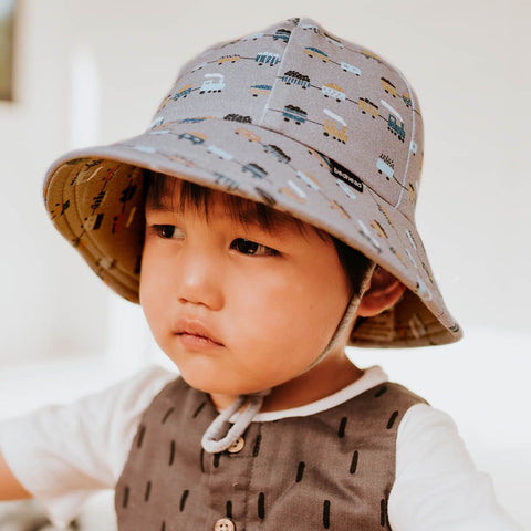 Child wearing a grey bucket hat with trains print.