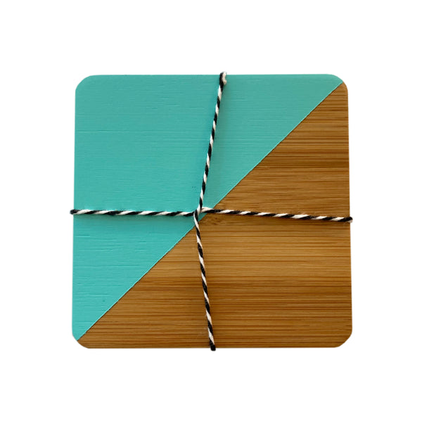 Bamboo coasters with one half diagonally dipped in turquoise paint, in a set of four tied together with black and white twine.