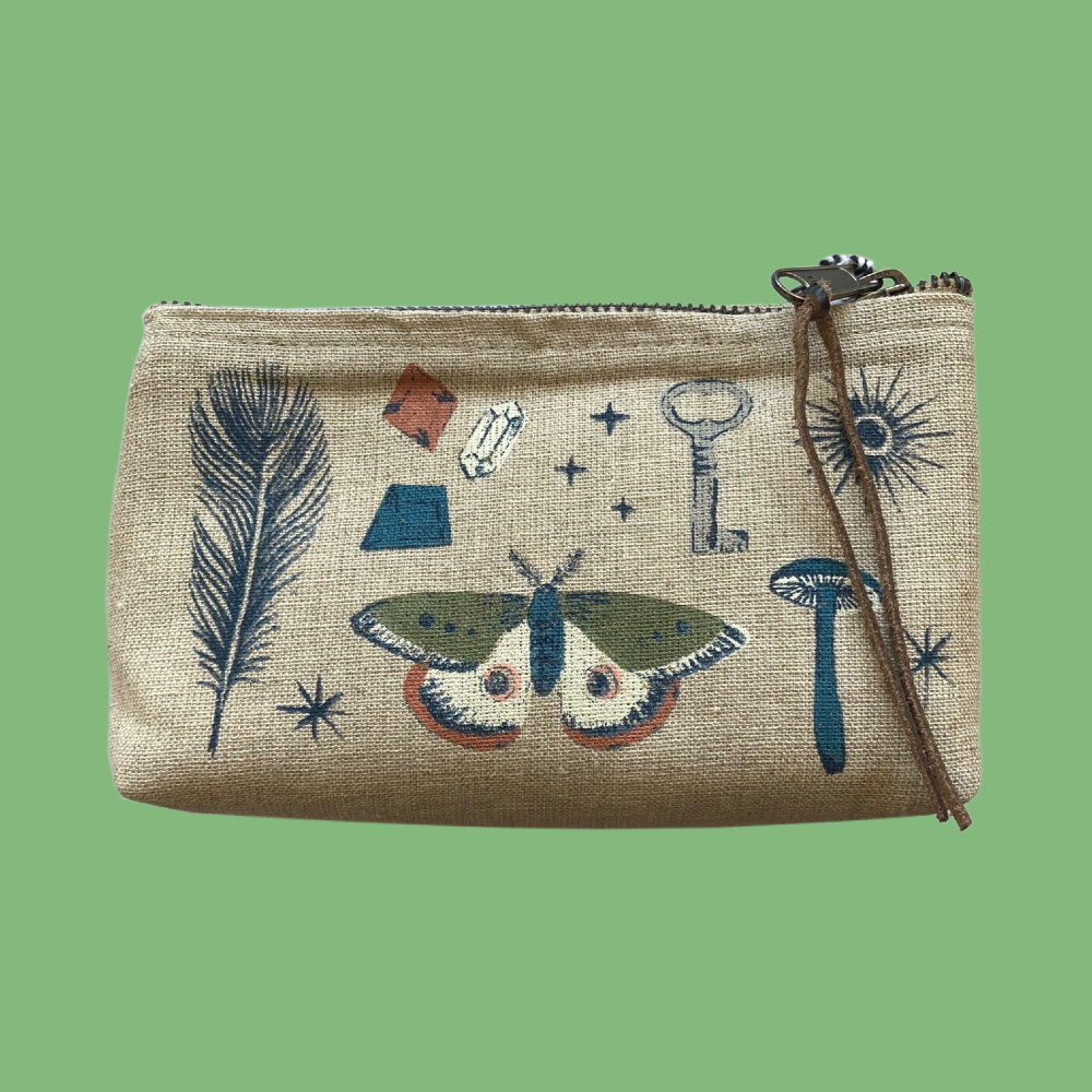 Image is of a linen pouch, with leather cord on its zip, and illustrations of a feather, moth, gems, key, mushroom and stars.