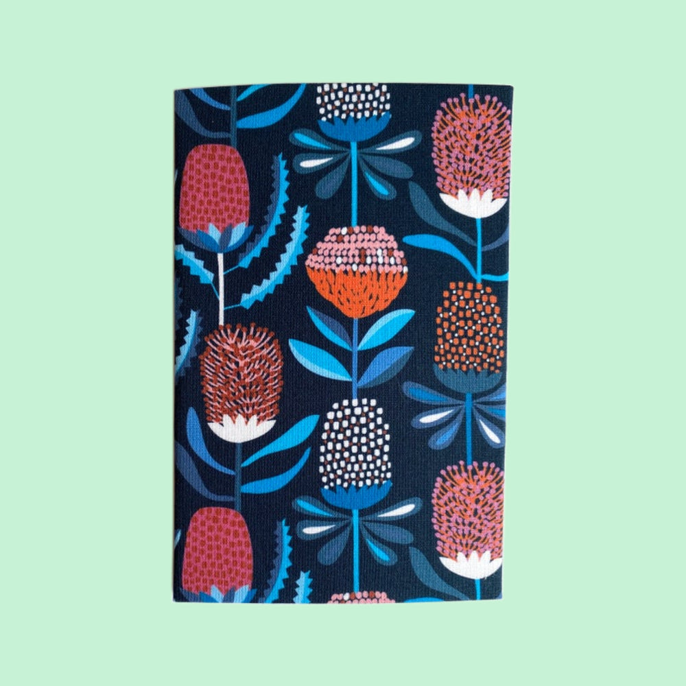Folded hanky with a dark blue and banksia floral print on a pale green  background