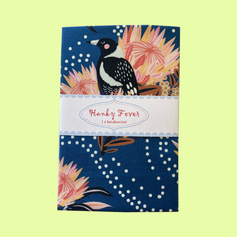 Folded hanky with dark blue floral and magpie design, on a pale yellow background