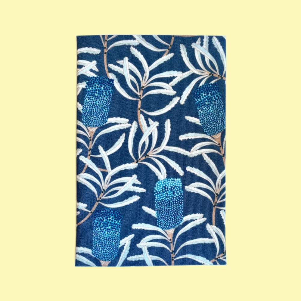 Folded hanky with a dark blue banksia print on a pale yellow background
