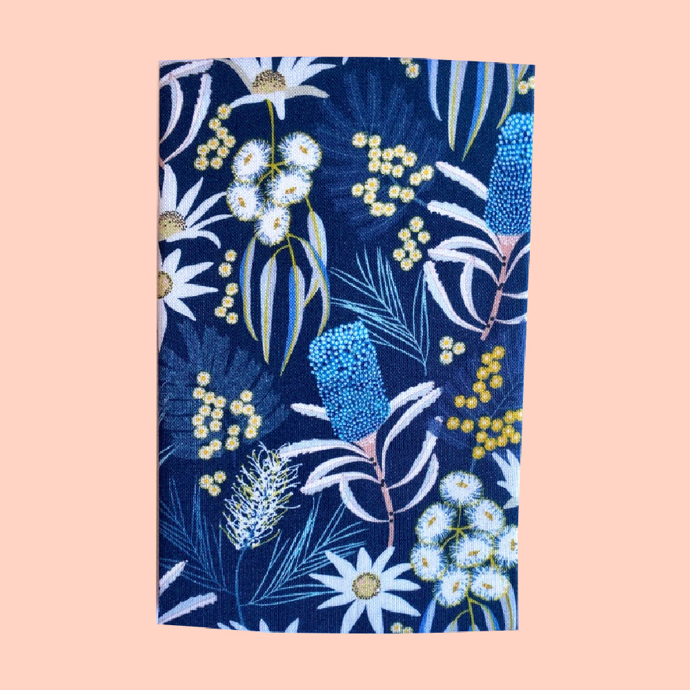 Folded hanky with a dark blue floral print on a pale pink background