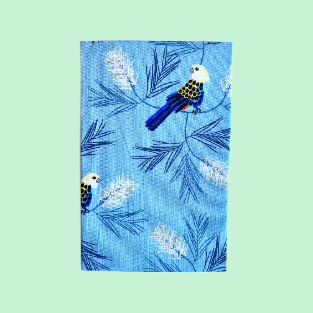 Folded hanky with a pale blue, rosella and floral print on a green background
