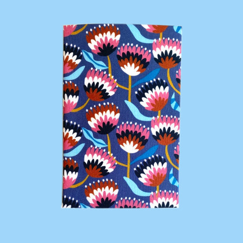 Folded hanky with a native Australian floral print, on a blue background