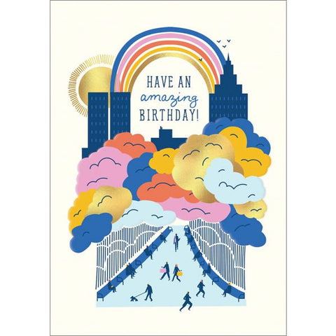 "Image is of a greeting card with an illustration of a city, shrouded in multicoloured clouds, with a rainbow and a gold foiled sun in the background. Text under the rainbow reads ""Have an amazing birthday!"""