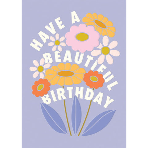 "Image is of a pale blue greeting card with a bunch of orange, pink and white flowers, with the text ""Have a beautiful birthday""."