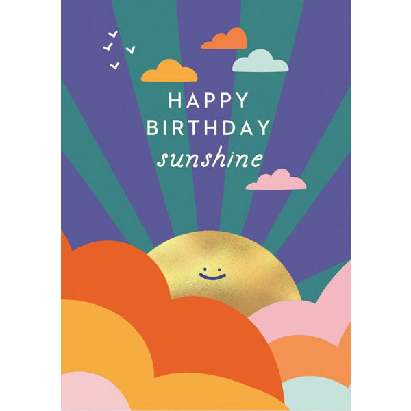 "Image is of a greeting card, covered in an illustration of a colourful sky with a gold foiled smiling sun. Text reads ""Happy Birthday sunshine""."