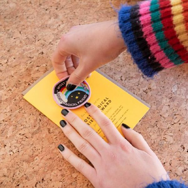 Image is of a pair of hands removing an iron-on patch from a yellow greeting card.