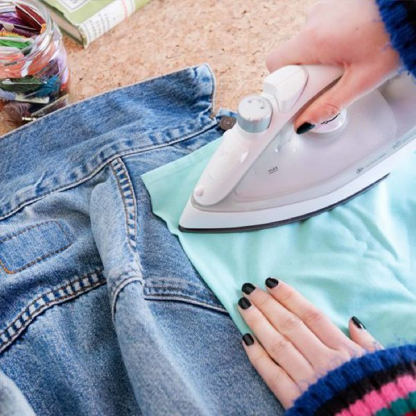 Image is of someone's hands as they iron on a patch to a denim jacket, with a piece of turquoise cloth between the iron and jacket.