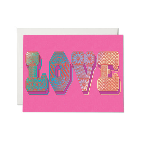 "Image is of a bright pink greeting card, with ""LOVE"" written in large letters, with a red and foiled patterned design, and a purple 3D effect detail. Behind the card is a matching white envelope."