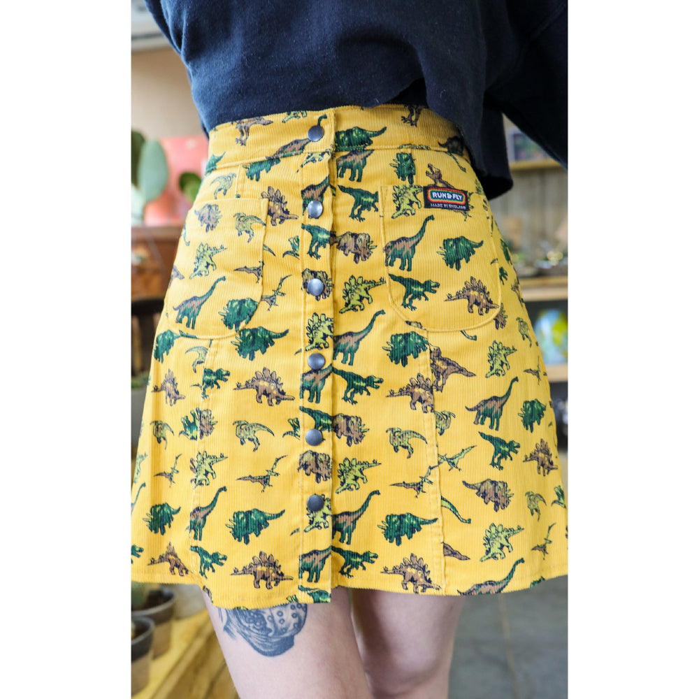 Photo of person wearing an A-line yellow corduroy skirt with buttons down the front, with a dinosaur print all over it.