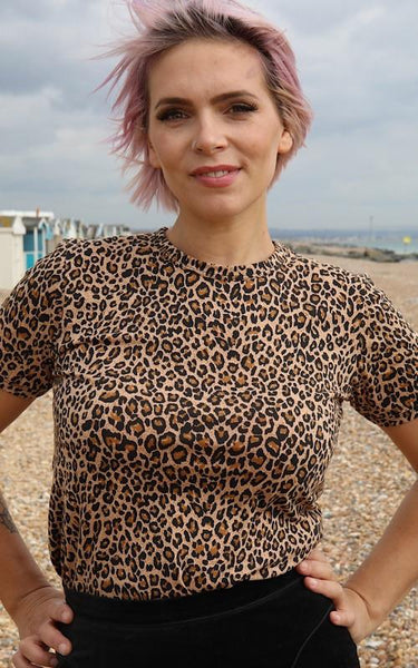 Image is of a person standing on a beach, with their hands on their hips, wearing a leopard print t shirt.