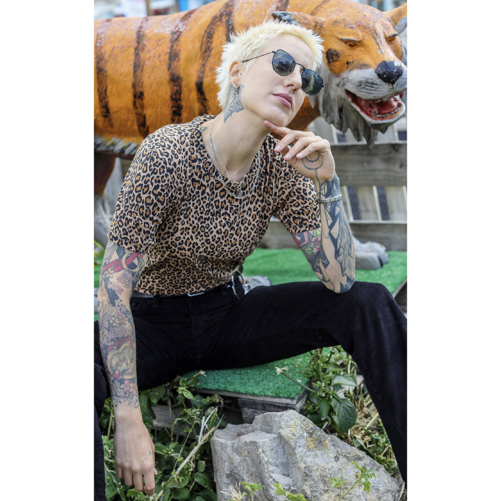 Image is of a person sitting with their hand under their chin, wearing a leopard print tee and black pants.