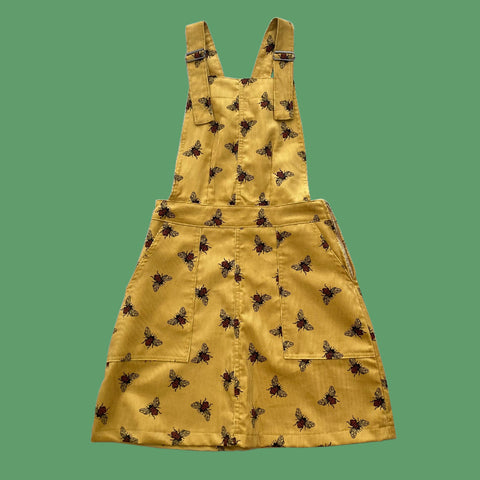 Gold corduroy pinafore with bee pattern.