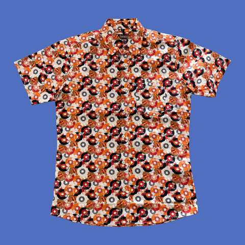 Short sleeved, button up shirt with an orange, black, white and red vinyl record print.