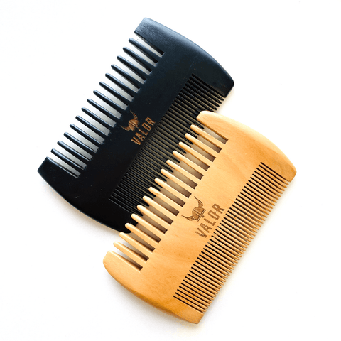 Image is of two cherry wood beard combs, one in natural finish and the other in black. Each comb has one side with wide-set teeth, and the other side has finer teeth. Photographed on a white background.