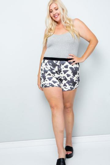 A woman wearing cow print shorts.