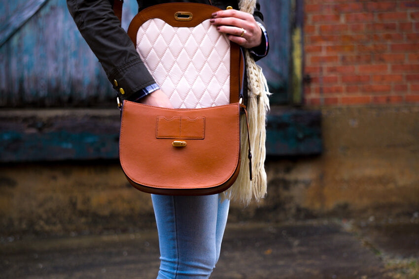 woman putting her hand into a brown leather purse
