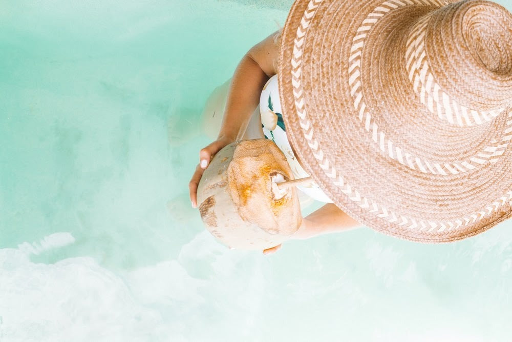 girl in a sun hat sipping from a coconut