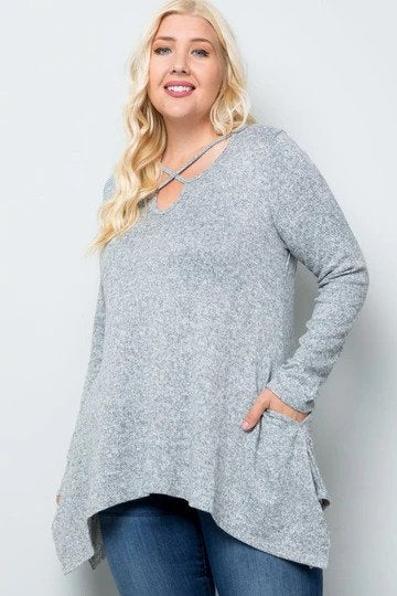 plus-sized woman wearing a light grey long-sleeve top with criss cross details