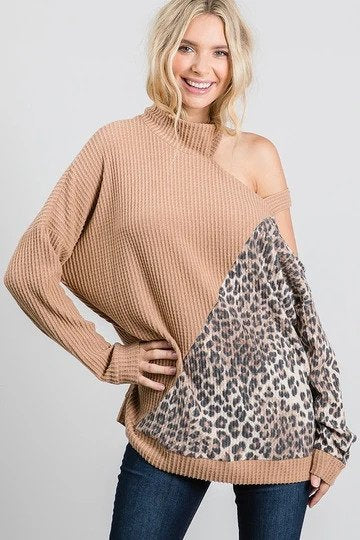 Woman wearing a tan and leopard print top