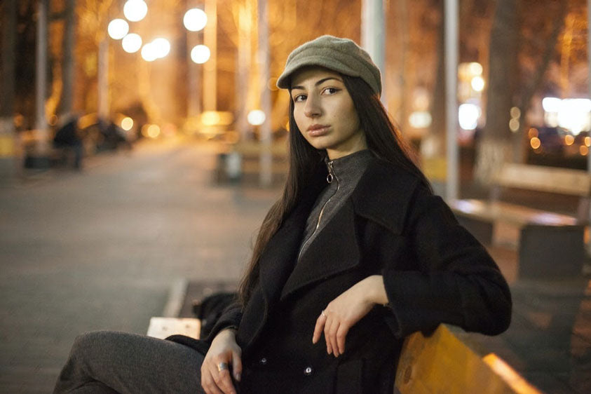 woman sitting on a bench wearing a peacoat and beret