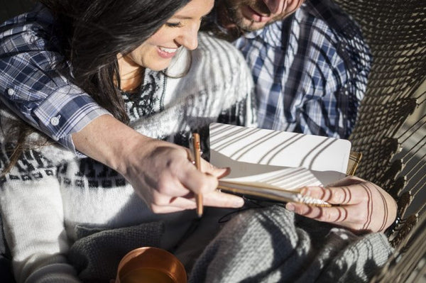 a couple writing in a journal together