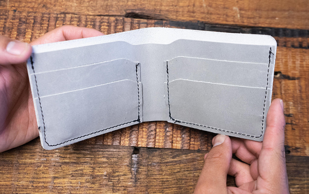 open bifold leather wallet in hands