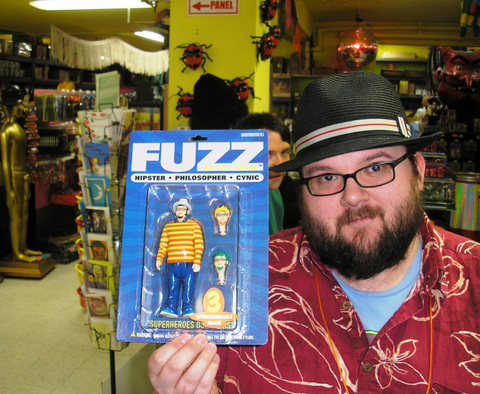 Fuzz holding a fuzz action figure in Archie McPhee store in wallingford