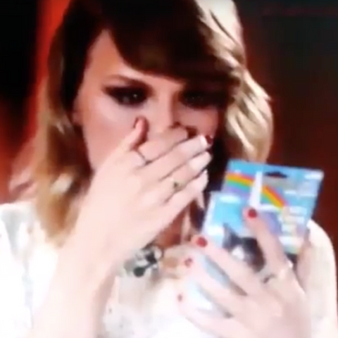 Taylor Swift covering her mouth in amazement at Inflatable Unicorn Horn for cats