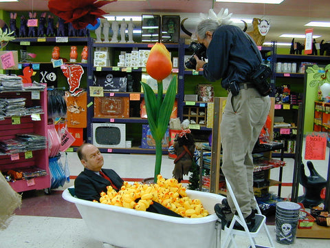 Mark Pahlow in a bathtub filled with Rubber devil ducks
