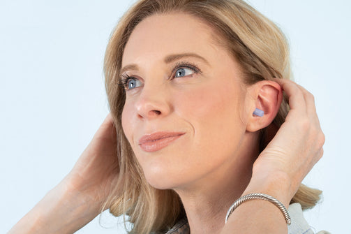 Picture of a woman with EarPlanes earplugs in her ear looking off into the distance.