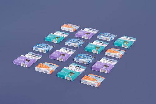 A rectangular array of 16 earplug packages including EarPlanes and WeatherX packages. Product is lying on a flat surface taken from a 45 degree angle.