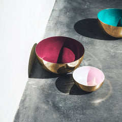 Metal bowls in the colors amethyst, rose and blue on a cemented floor.
