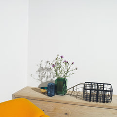 A wooden bookcase decorated with a small metal bowl, colorful glass vases and metal frame basket.