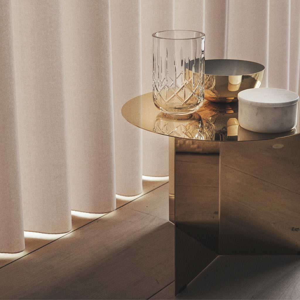 Golden side table beautifully decorated with a metal bowl with grey enamel, a crystal clear vase and a white marble bowl.