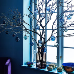 windowsill with decorative branches and blue metal bowls.