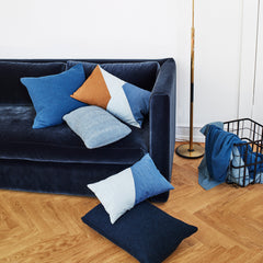 Five cushions in different shades of blue on top of a blue velvet sofa.