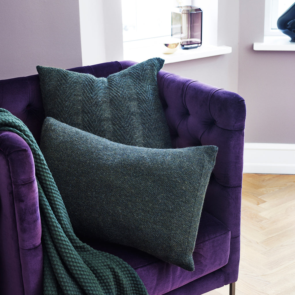 Army green cushions on a purple armchair.