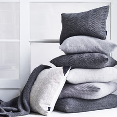 Stacked knitted baby alpaca wool cushions in different shades of grey.